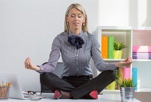 photodune-9145247-young-woman-sitting-in-lotus-yoga-pose-on-desk-xs