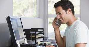 photodune-339303-man-in-home-office-on-telephone-using-computer-and-smiling-xs-2